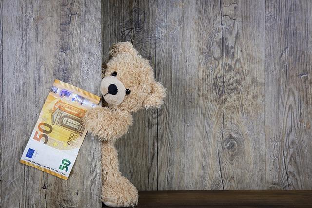 お金を握ったクマの人形